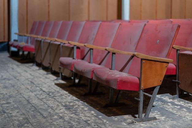 Fila di sedili di un vecchio cinema abbandonato Foto Premium