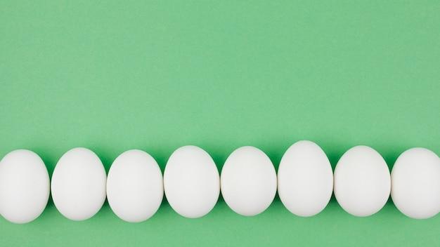 Fila di uova di gallina bianca sul tavolo verde Foto Gratuite