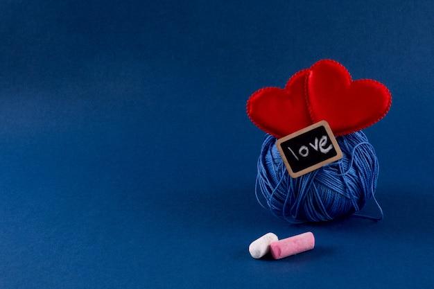 Filati per maglieria blu con i cuori rossi sul fondo blu classico di colore 2020. san valentino 14 febbraio concetto fai da te. copia spazio, vista dall'alto, banner. Foto Premium