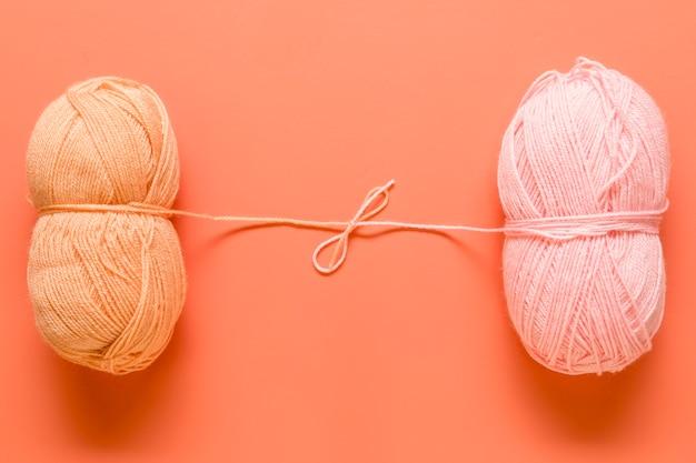 Filato per maglieria legato in arco su sfondo arancione Foto Gratuite