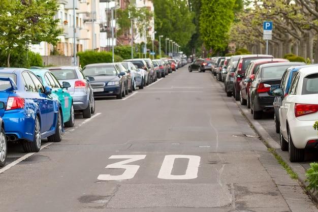 File di auto parcheggiate sul ciglio della strada nel quartiere residenziale Foto Premium