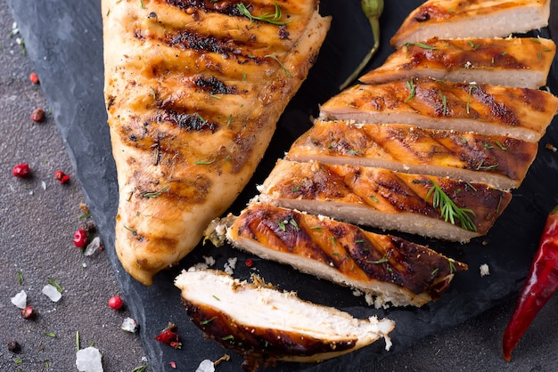 Filetti di pollo alla griglia sul piatto di ardesia su sfondo grigio cemento Foto Premium