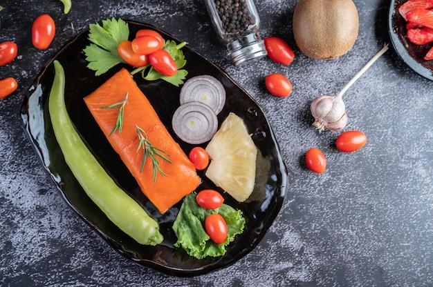 Filetti di salmone crudo, pepe, kiwi, ananas e rosmarino su un piatto e pavimento in cemento nero. Foto Gratuite