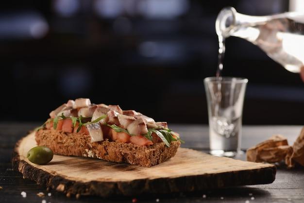 Filetto di aringhe con pomodoro su un pezzo di pane fritto. su un piatto blu Foto Premium