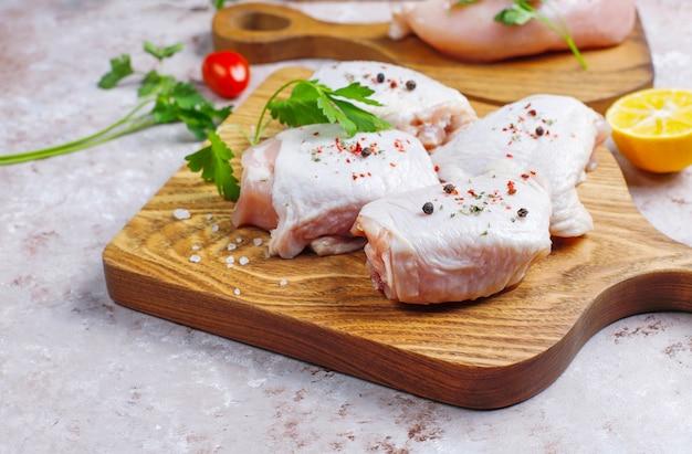Filetto di carne di pollo crudo, coscia, ali e zampe con erbe, spezie, limone e aglio. vista dall'alto Foto Premium