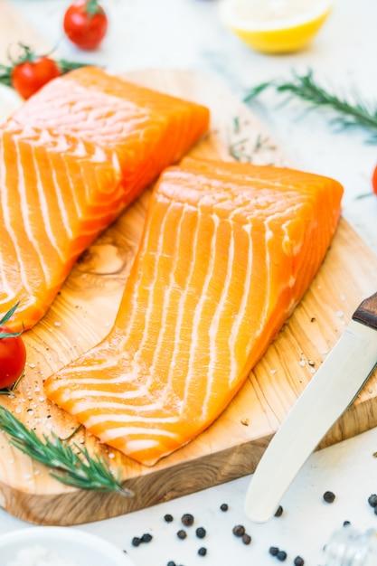 Filetto di carne di salmone crudo e fresco sul tagliere di legno Foto Gratuite