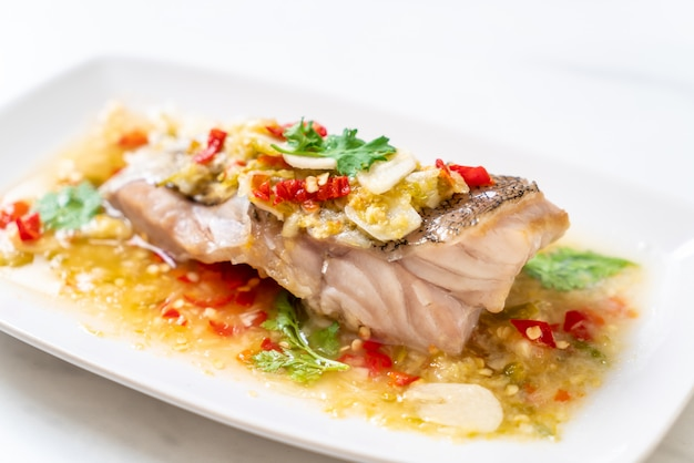 Filetto di pesce di cernia al vapore con salsa al lime e peperoncino condita con lime Foto Premium
