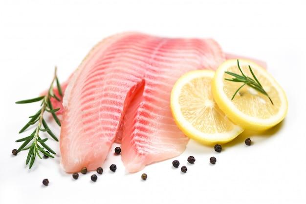 Filetto di pesce fresco affettato per bistecca o insalata con erbe spezie rosmarino e limone - filetto di tilapia crudo su sfondo bianco e ingredienti per cucinare cibo Foto Premium