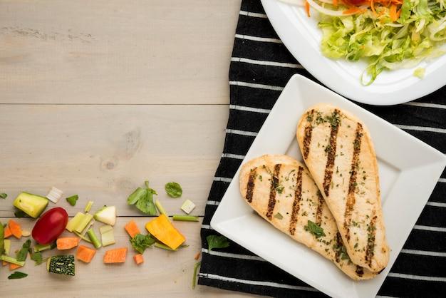 Filetto di pollo alla griglia con insalata e pezzi di verdura sparsi sulla scrivania in legno Foto Gratuite