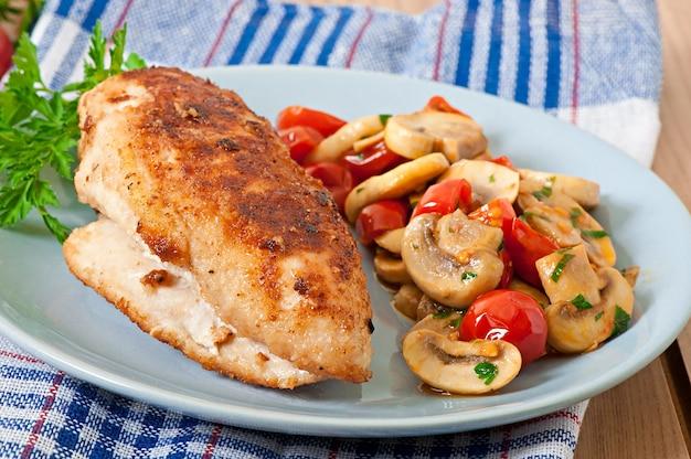 Filetto di pollo con pangrattato croccante guarnito con funghi e pomodori Foto Premium