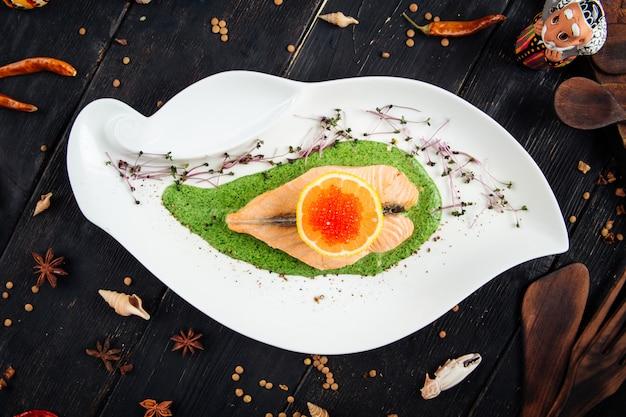 Filetto di salmone con spinaci e caviale di uova di limone rosso Foto Premium