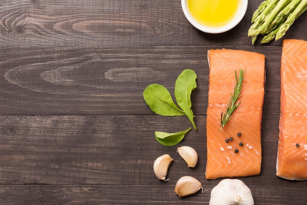 Filetto di salmone fresco con spezie su fondo in legno Foto Premium