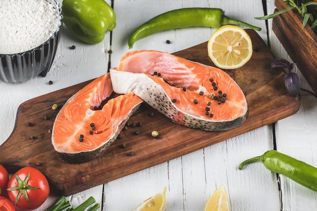 Filetto di salmone sulla tavola di legno con limone e pomodoro con peperoncini verdi Foto Gratuite