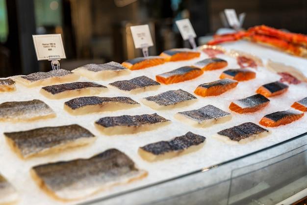 Filetto di una varietà di pesce fresco sul ghiaccio in una finestra del ristorante. pescato fresco. Foto Premium