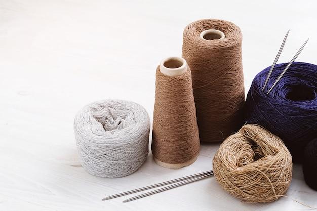 Fili multicolori, matasse e grovigli di filati di lana italiana, ferri da maglia. il concetto di lavoro a maglia, cucito, fatto a mano. Foto Premium