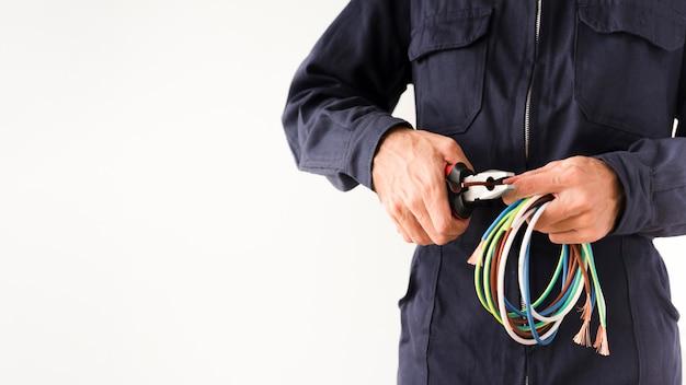 Filo di taglio elettricista attraverso la pinza su sfondo bianco Foto Gratuite