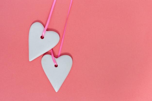 Fine bianca colorata di due orecchie ceramiche dei cuori su sul rosa di carta Foto Premium