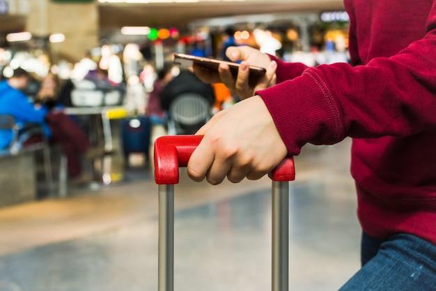 Fine della mano della ragazza su che tiene la maniglia rossa della valigia Foto Premium