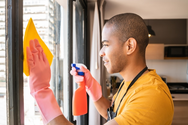 Finestra di vetro di pulizia della governante maschio a casa. Foto Gratuite