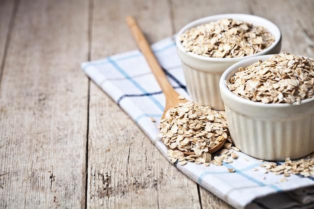 Fiocchi d'avena in ciotole di ceramica e cucchiaio di legno sul tovagliolo di lino, spighe di grano dorato Foto Premium