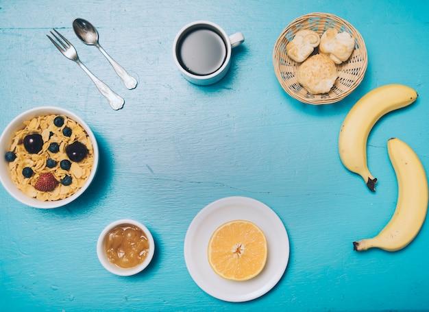 Fiocchi di mais; marmellata; arancia dimezzata; pane; caffè; banana sul contesto in legno blu Foto Gratuite
