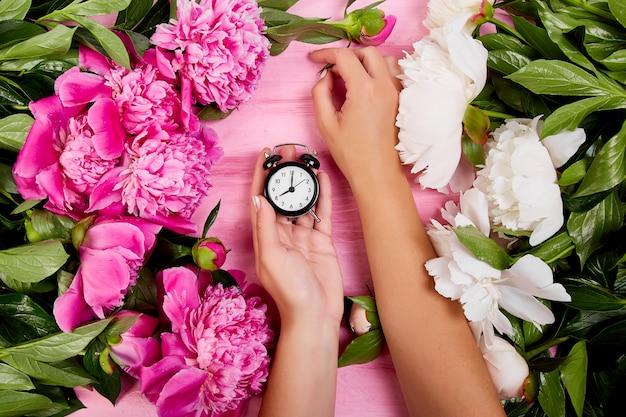 Fioraio al lavoro, le mani della donna tengono la sveglia. Foto Premium