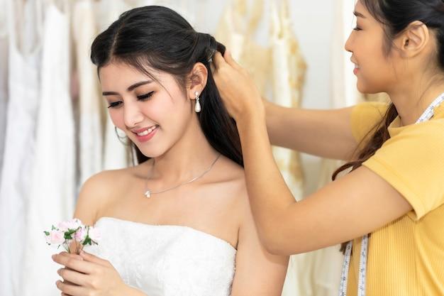 Fiore asiatico della tenuta della donna che misura sul vestito da sposa in un negozio dal sarto. Foto Premium