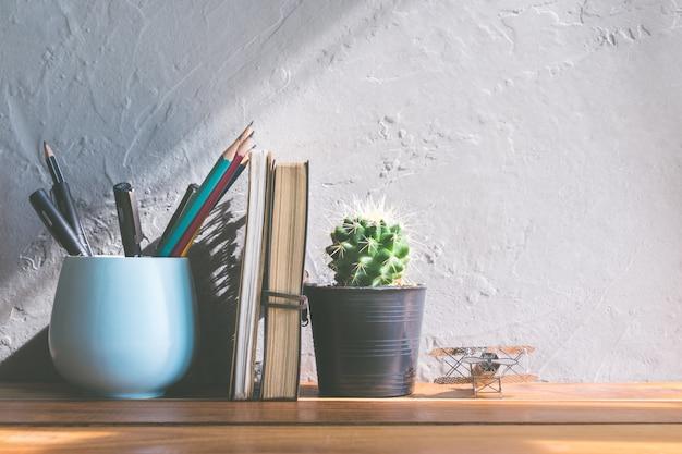 Fiore del cactus con il taccuino sul concetto interno moderno del fondo della tavola di legno dell'ufficio. Foto Premium
