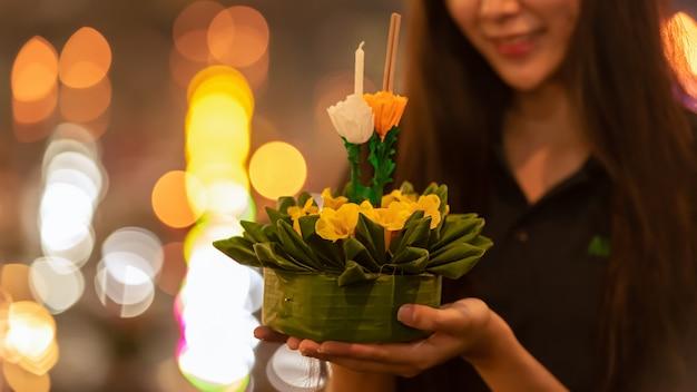 Fiore di loto di carta con la candela che galleggia su un fiume alla notte nel festival del krathong di loy Foto Premium