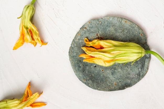 Fiore di zucca essiccato vista dall'alto con tortilla di spinaci Foto Gratuite