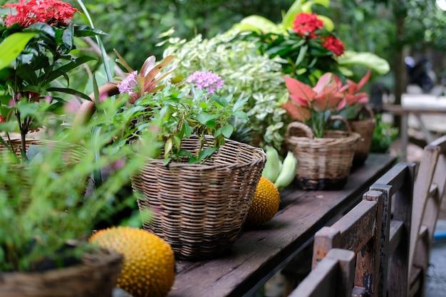 Fiore e foglie di piante verdi nel cesto di vimini decorare sul balcone della terrazza Foto Premium