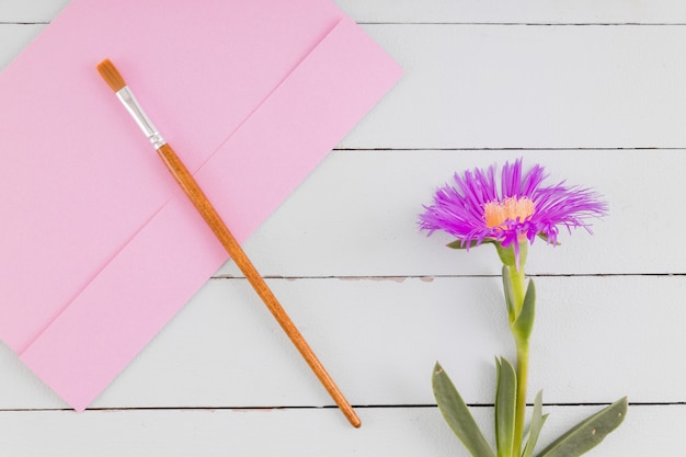 Fiore e spazzola di vista superiore su fondo di legno Foto Gratuite