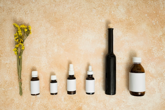 Fiore giallo del limonium con le file delle bottiglie di olio essenziale su fondo strutturato beige Foto Gratuite