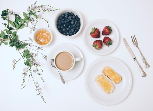 Fiore; marmellata; mirtillo; fragola; tazza di caffè e pane tostato su sfondo bianco con posate Foto Gratuite