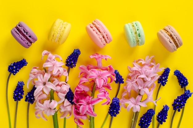 Fiori blu del muscari, giacinto rosa e macarons o amaretti su fondo giallo. colpo di testa. distesi. concetto di celebrazione Foto Premium