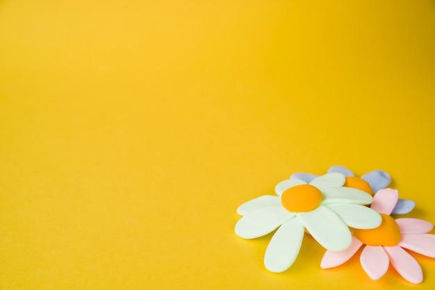 Fiori colorati pastello piani su fondo giallo Foto Gratuite