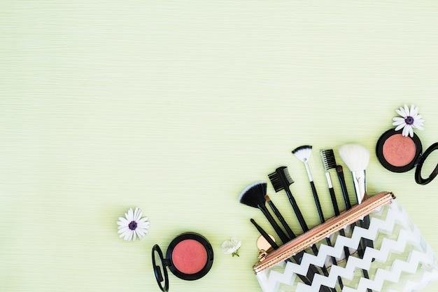 Fiori con pennelli per il trucco e cipria compatta su sfondo verde menta Foto Gratuite
