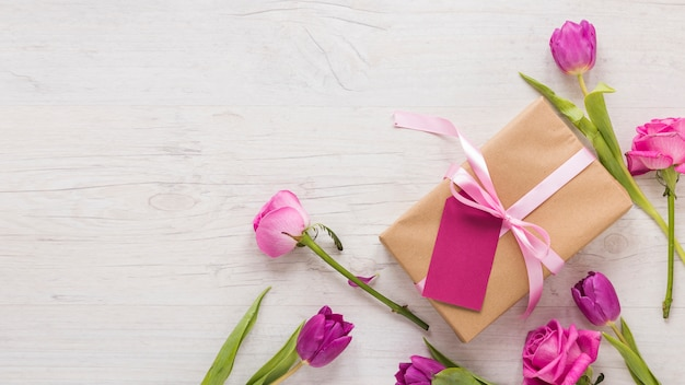 Fiori con scatola regalo sul tavolo luminoso Foto Gratuite