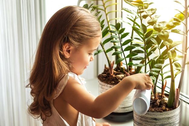 Fiori d'innaffiatura della bambina a casa Foto Premium