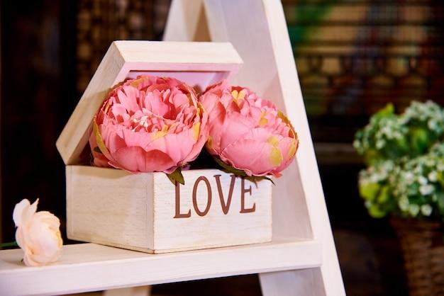 Fiori decorativi in scatola di legno sul rack. Foto Premium