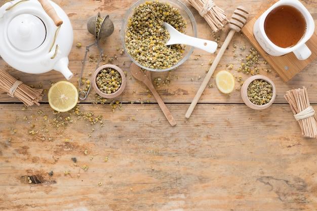 Fiori di crisantemo cinese essiccati; teiera; colino da tè; mestolo al miele; contenitore e tè al limone fresco sul tavolo di legno Foto Gratuite