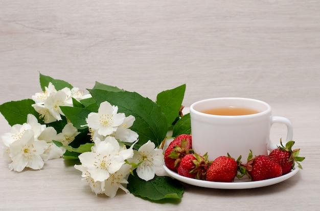 Fiori di gelsomino, tazza bianca con tè, fragole, primo piano Foto Premium