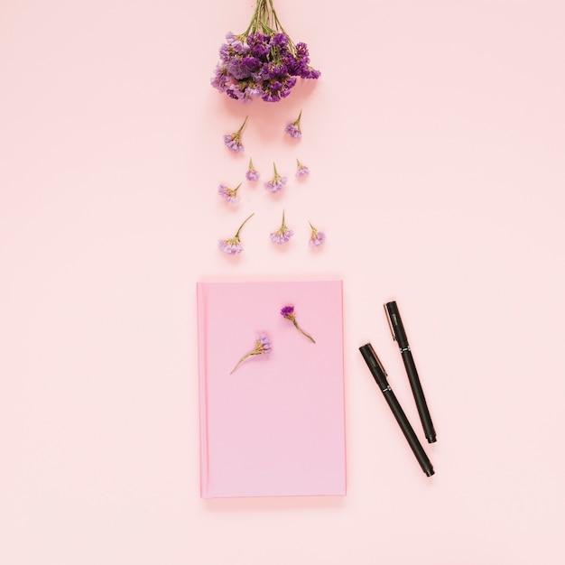 Fiori di lavanda sopra il libro rosa e due pennarelli su sfondo colorato Foto Gratuite