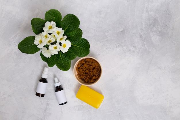 Fiori di primula; bottiglie di olio essenziale; sapone giallo e polvere di caffè in una ciotola sullo sfondo di cemento Foto Gratuite