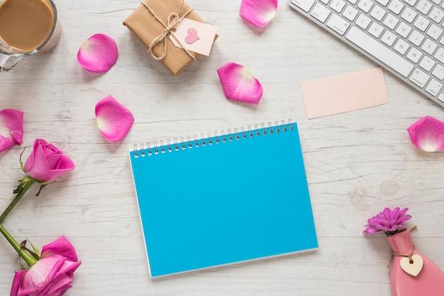 Fiori di rosa con scatola regalo e blocco note sul tavolo Foto Gratuite
