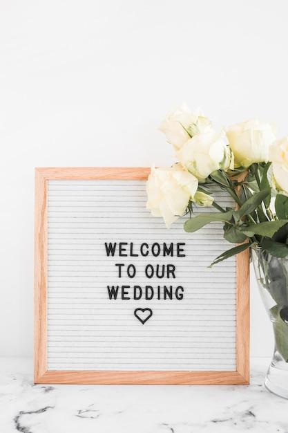 Fiori di rose bianche in vaso e bacheca di benvenuto per il matrimonio Foto Gratuite
