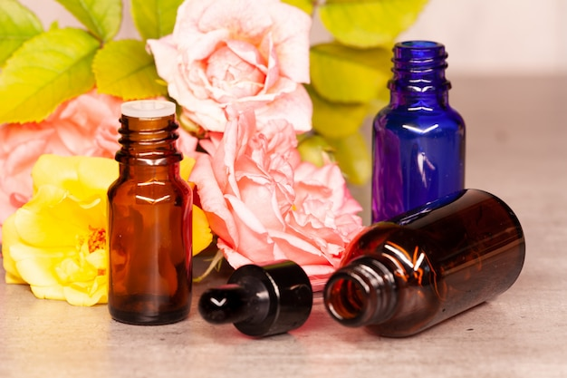 Fiori di rose e bottiglie di olii essenziali per aromaterapia Foto Premium