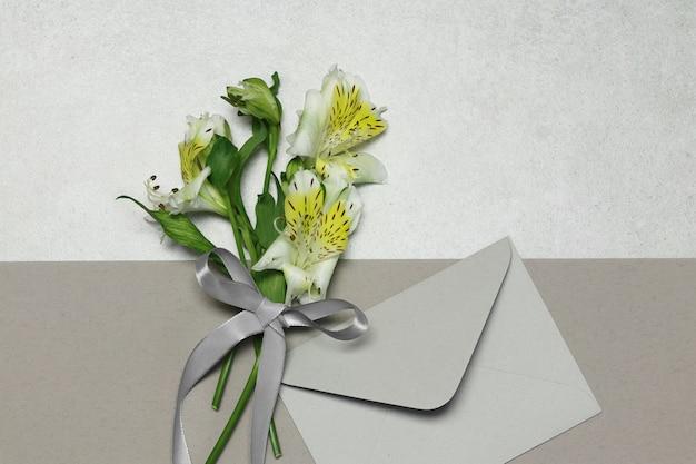 Fiori e busta su sfondo beige grigio Foto Premium