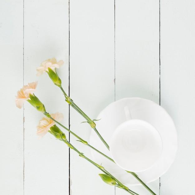 Fiori e tazza di vista superiore su fondo di legno Foto Gratuite