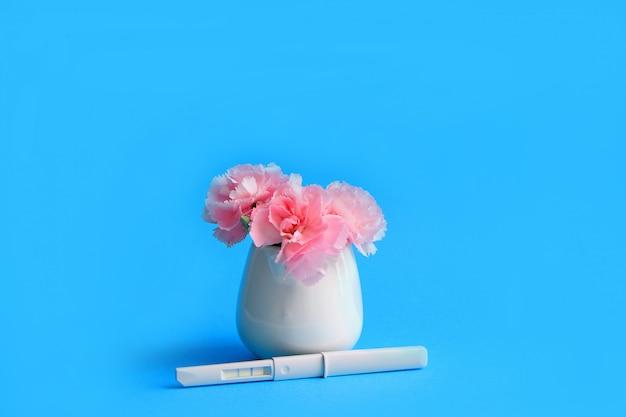 Fiori e test di gravidanza su uno sfondo blu Foto Premium